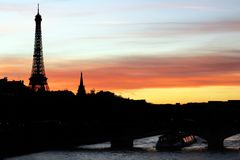 Eiffel tower silhouette and the river Seine at a Parisian pinky orange sunset. The Eiffel tower silhouette and the Seine River in Paris, France, cityscape with a stock photo
