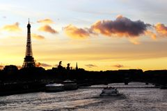 Eiffel tower silhouette and the river Seine at a Parisian sunset. The Eiffel tower silhouette and the Seine River in Paris, France, cityscape with a tourists stock image
