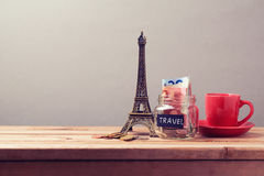 Eiffel Tower souvenir and money box on wooden table. Planning summer vacation, money budget trip Royalty Free Stock Photos