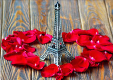 Eiffel tower. Statue and heart shaped red rose petals on wooden background. Travel, love concept. St Valentine's Day Stock Photography