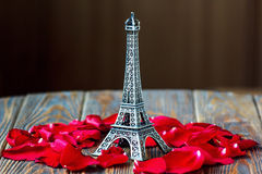 Eiffel tower. Statue and red rose petals on wooden background. Travel, love concept. St Valentine's Day Royalty Free Stock Photography