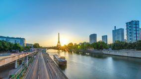 Eiffel Tower sunrise timelapse with boats on Seine river and in Paris, France. View from Grenelle bridge. Modern buildings and traffic on a road stock footage
