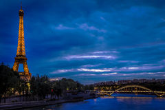 The Eiffel Tower after sunset. An evening view of the Eiffel Tower and the Pont Debilly over the Seine River in Paris, France Stock Images