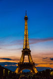 Eiffel Tower at sunset in Paris. PARIS, FRANCE - JULY 14 2014: Eiffel Tower at sunset is the most visited monument in France and the most famous symbol of Paris Royalty Free Stock Photo