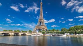 The Eiffel tower timelapse hyperlapse from embankment at the river Seine in Paris. Ship and boats on river at sunny summer day
