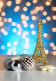 Eiffel Tower toy with Christmas / New Year decorations, ornaments. Blue golden bokeh background. Royalty Free Stock Photo