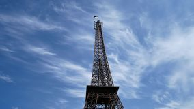 The Eiffel Tower over blue sky. The Eiffel Tower with the Ukrainian flag on top stock video