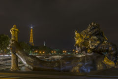 Eiffel Tower view and a statue from Pont Alexandre III at night royalty free stock image
