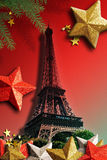 The Eiffel Tower for Xmas. A retro stylized Eiffel Tower on a red to grey background. Xmas stars in red, gold & silver are decorated around it. Some pine Royalty Free Stock Photo