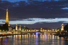 Eiffeltorn och Alexander III bro på natten Arkivfoto