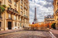 Eiffeltorn som ses från gatan i Paris, Frankrike Abstrakt bakgrund av kullerstentrottoar