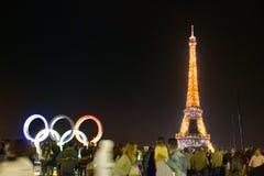 Eiffeltorn, turister i natttimmar och olympiska symboler Royaltyfri Foto