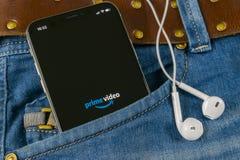 In eigen zak steekt het eerste video de toepassingspictogram van Amazonië op Apple-iPhone X het scherm in jeans Het eerste videoa stock fotografie