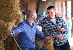 Eigenaren van een ranch die in een loods spreken stock foto's