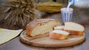 Eigengemaakt brood, melk en rijpe oren van rogge op een houten achtergrond stock videobeelden