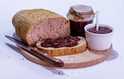 Eigengemaakt brood met aardbeijam op houten plaat Stock Afbeelding