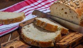 Eigengemaakt brood met zonnebloemzaden, scherp raad en mes royalty-vrije stock afbeeldingen