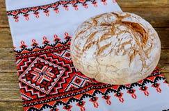 eigengemaakt brood op Oekraïens borduurwerk een houten lijst stock afbeelding
