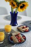 Eigengemaakt die ontbijt met pannekoeken met aardbeienjus d'orange en zonnebloemen worden bedekt stock foto's