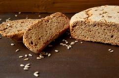 Eigengemaakt gesneden vers brood met zonnebloemzaden op de houten achtergrond klaar te eten Gebakken enkel smakelijk brood op de  stock afbeeldingen