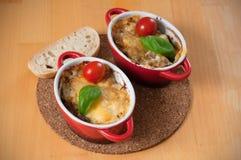 Eigengemaakt julien met paddestoelen in twee rode, hete kommen Kip met paddestoelen met kaas op de houten lijst worden gebakken d stock foto's