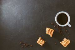 Eigengemaakt ontbijt, steen zwarte lijst De Weense wafels gebroken stukken, een kop van koffie, verspreidden koffiebonen, hoogste stock fotografie