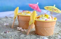 Eigengemaakt vanilleroomijs op het gele strand van de zandzomer Wit bevroren heerlijk dessert in individuele jellovaas stock afbeeldingen