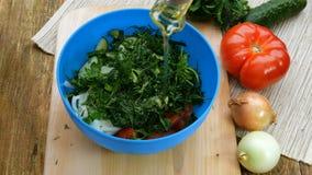 Eigengemaakt vegetarisch gezond voedsel De menselijke handen gieten tafelolie van een kruik op tomaten, komkommers, uien, dille e stock video
