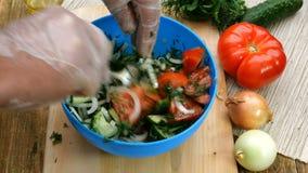Eigengemaakt vegetarisch gezond voedsel De menselijke handen mengen tomaten, komkommers, uien, dille en peterselie, voor de voorb stock footage