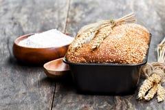 Eigengemaakt volkorenroggebrood in bakselvorm op houten lijst stock afbeelding
