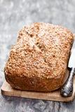 Eigengemaakt volkorenroggebrood met lijnzaad op houten lijst stock foto
