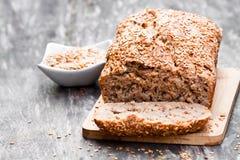 Eigengemaakt volkorenroggebrood met lijnzaad op houten lijst stock afbeeldingen