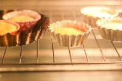 Eigengemaakt zoet muffinbaksel in vormen in oven royalty-vrije stock foto's