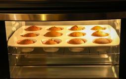 Eigengemaakt zoet muffinbaksel in vormen in oven stock fotografie
