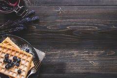 Eigengemaakte Belgische wafels met bosbessen op het donkere houten lusje stock foto's