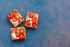 Eigengemaakte Belgische wafels met room en verse aardbeien op een roze-blauwe achtergrond Hoogste mening, exemplaarruimte royalty-vrije stock afbeeldingen