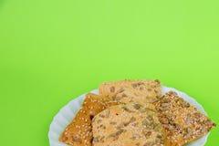 Eigengemaakte bij op een groene achtergrond kernachtig brood met zonnebloem, vlas en sesamzaden Dieet koekjes stock foto's