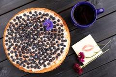 Eigengemaakte bosbessenpastei met een kop koffie en bloemen Lippenpri Stock Afbeeldingen