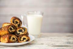Eigengemaakte broodjes met papaverzaden in witte plaat en kop van melk op lichte houten lijst Selectieve nadruk royalty-vrije stock afbeelding
