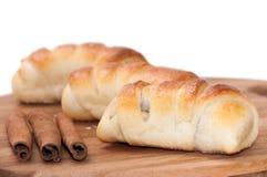 Eigengemaakte broodjes met room en gepoederde suiker en pijpjes kaneel Royalty-vrije Stock Foto
