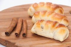 Eigengemaakte broodjes met room en gepoederde suiker en pijpjes kaneel Royalty-vrije Stock Afbeeldingen