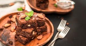 eigengemaakte, chocoladebrownie met hazelnoten en amandelen in een houten plaat op een zwarte achtergrond stock foto