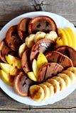 Eigengemaakte chocoladepannekoeken met stroop, gesneden verse bananen en appelen op een witte plaat Stock Foto