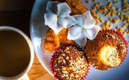 Eigengemaakte de bakkerij, de banaan cupcakes met witte sesamzaden en pinda's het bedekken dienden met verse koffie voor ontbijt stock fotografie