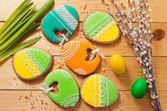 Eigengemaakte de peperkoekkoekje en eieren van Pasen over houten lijst stock foto