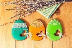 Eigengemaakte de peperkoekkoekje en eieren van Pasen over houten lijst stock afbeelding