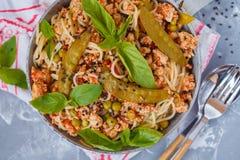 Eigengemaakte deegwarenspaghetti met kippengehakt, groene erwten en stock afbeeldingen