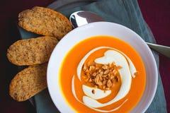 Eigengemaakte die bataat en wortelsoep met Spaanse pepers en gember door zure room worden verfraaid en geroosterde pinda in witte Royalty-vrije Stock Afbeeldingen