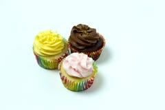 3 eigengemaakte die cupcakes op een witte achtergrond wordt geïsoleerd Stock Fotografie