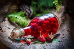 Eigengemaakte die frambozenlikeur van vruchten en alcohol wordt gemaakt royalty-vrije stock afbeelding